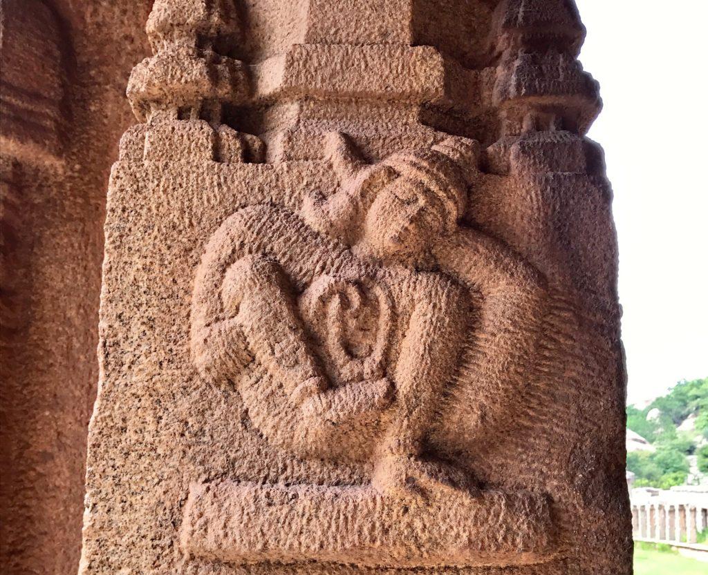 Niemy świadek historii jogi. Wyrzeźbiona postać ma lewą nogę założoną za głowę i unosi się, balansując na lewej dłoni. Prawa ręka podtrzymuje pod kolanem prawą nogę. W prawej dłoni trzyma przedmiot wyglądający, jak medytacyjna mālā. Wnioskując z ułożenia włosów można przypuszczać, że mamy dotyczenia z przedstawicielem średniowiecznych Nath Joginów. Jak długo jogin ten pozostawał w tej pozycji? Czy recytował mantry podczas praktyki, korzystając z trzymanej w ręku māli? Jakie inne pozycje mógł praktykować? Na te pytania nie znamy dzisiaj odpowiedzi. Świątynia Achyutaraya, XV-XVI wiek, Karnataka. Zdjęcie: Seth Powell